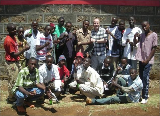 Gary Harper with young men in rural Thigio, Kenya after a workshop for the AMKA (Awakening Men for Knowledge and Action) health prevention intervention that Harper and his team co-developed with men from the community. The intervention is focused on decreasing substance use and gender-based violence and increasing safe sexual behaviors.