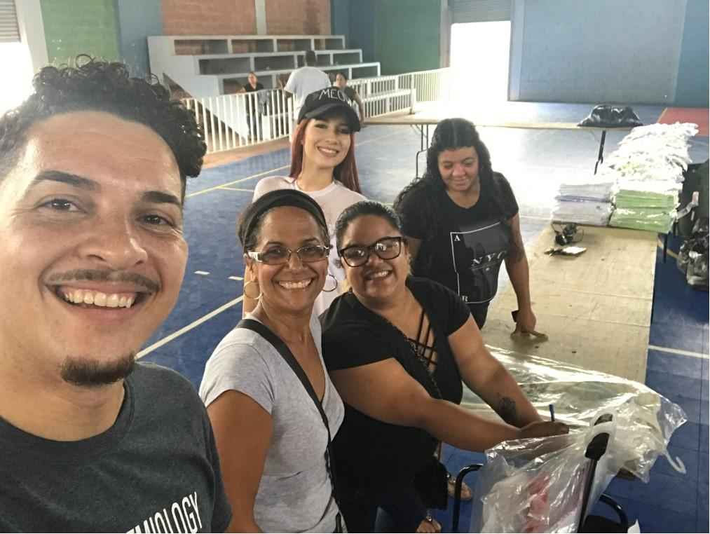 A selfie while setting up tables for food, hygiene packages, and clothing. Left to right: Matos-Moreno, community team leader Nylmarie, Melba, Matos-Moreno's sister Marisol, and a municipality worker volunteering at the event. In the background are clothes that were given away and suitcases used to transport the hygiene packages.