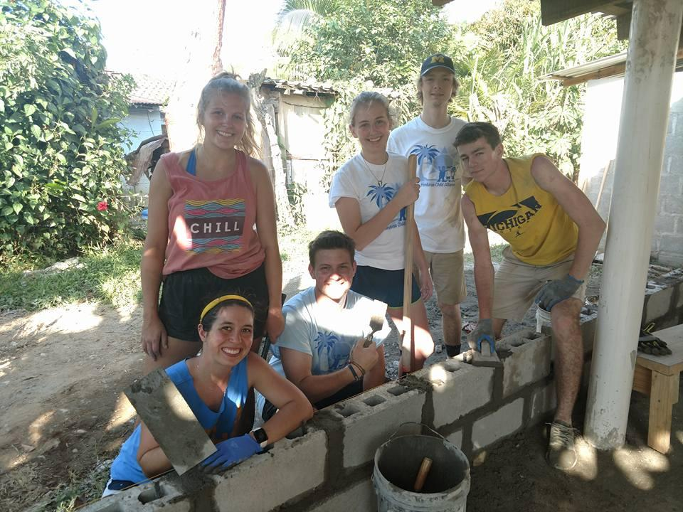 Madison (left, standing) learned how to lay bricks from a contractor on her first day in Honduras. The group was building walls for a patio they constructed on the back of a school to provide shade for students.