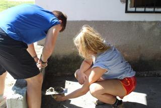 Madison (right) and a fellow volunteer applying cement in preparation of laying bricks to school patio.