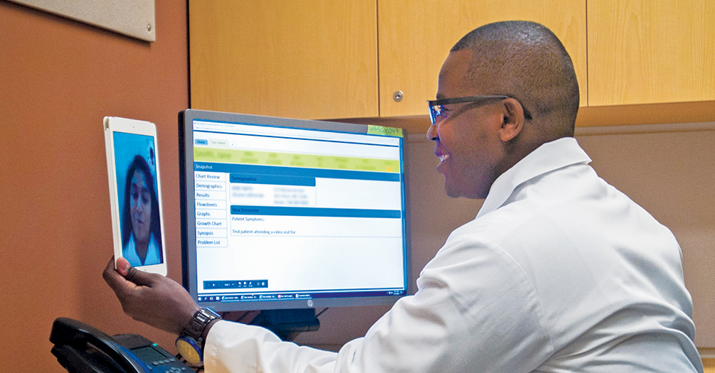Stanley Gitau Mukundi, a physician assistant at Michigan Medicine, conducts a telehealth visit with a patient. Photo from Michigan Medicine, University of Michigan