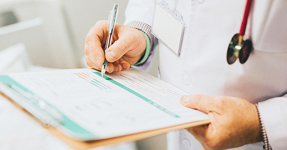 A doctor writes on a clipboard