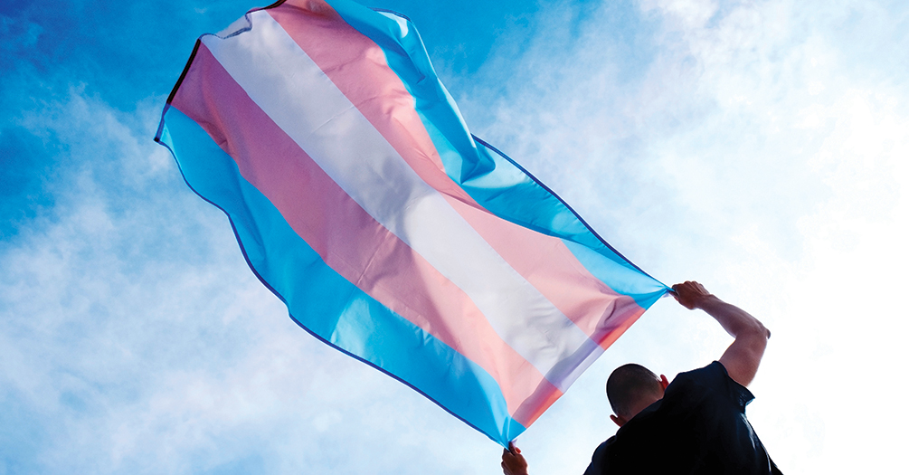 A young person flies a transgender flag
