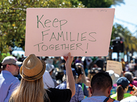 "Demonstrators at a rally holding signs, one that reads ""keep families together"""