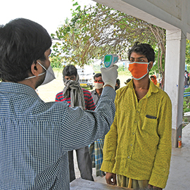 A health screener in India directs a thermometer at a patient