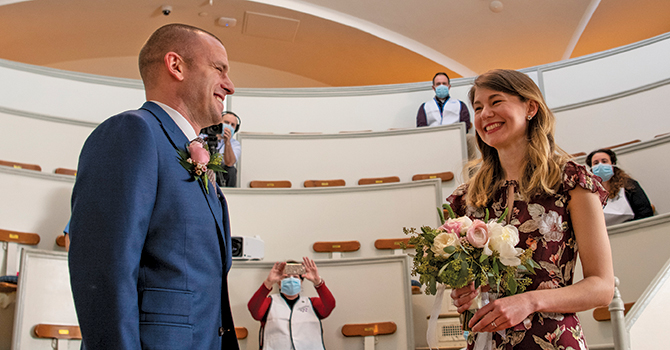 Jen Andonian, MPH '15 and Matt Shearer, MPH '14, pause on a busy work day in March, with a team of frontline-workers-turned-wedding-guests, to get married in the historic Ether Dome surgical theatre at Massachusetts General Hospital, just days after they had canceled their well-planned wedding.