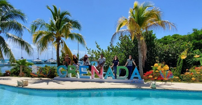 Group photo of students standing with Grenada letters