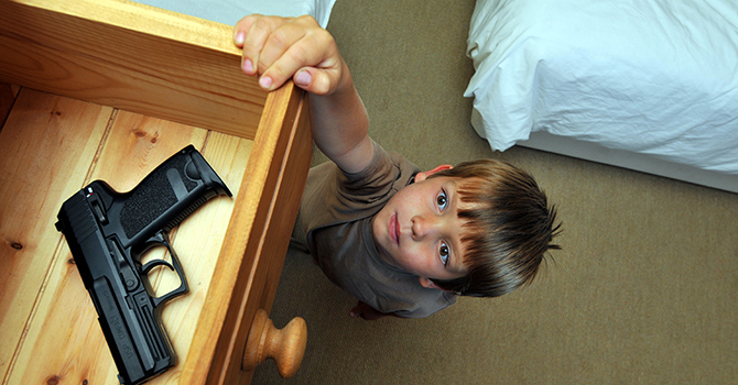 Child reaching into drawer with gun