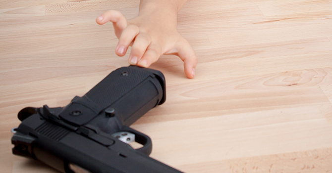 child reaching for a gun left on a wooden table