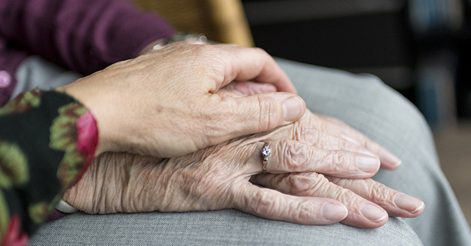 hands of caregiver and an elderly woman