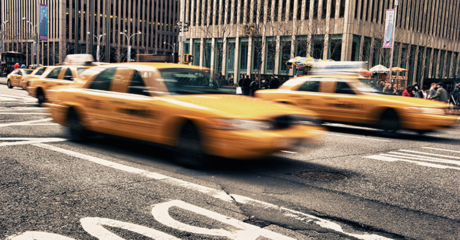 Taxis moving quickly down a street in New York City