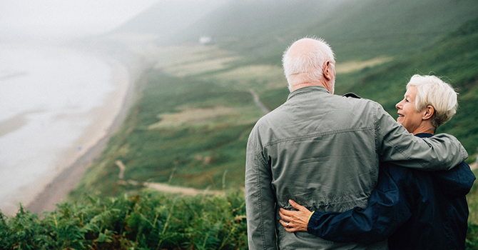 Older couple hiking, smiling and talking while looking over the countryside