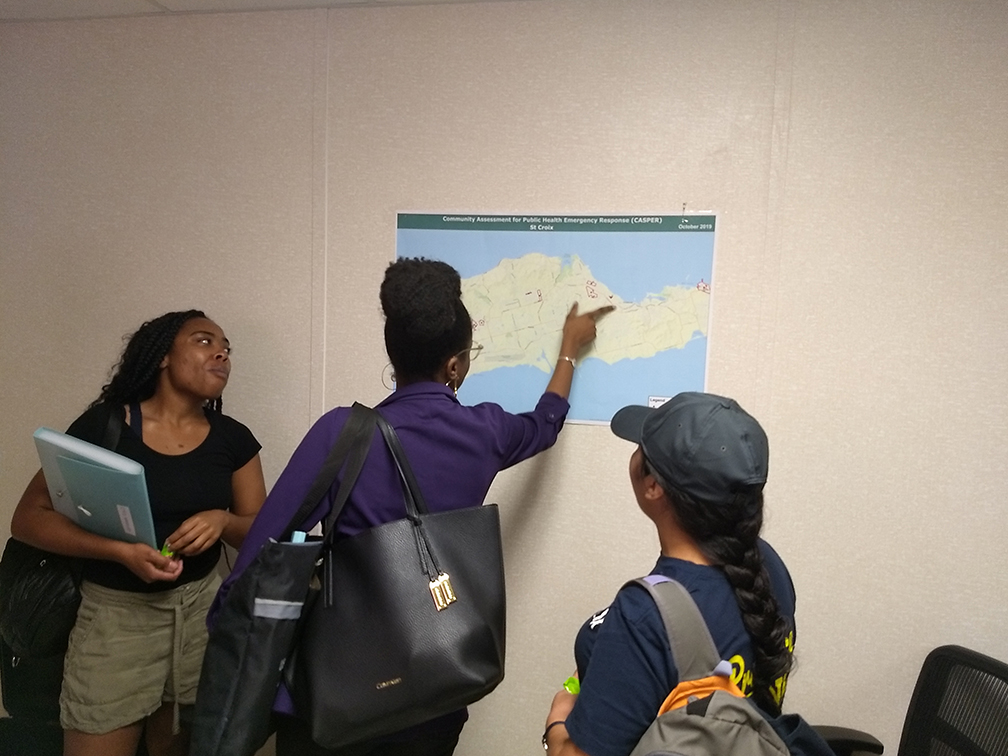 Kayla Hunter and Quetzabel Benavides with community partner at Department of Health examining map of St. Croix survey clusters.