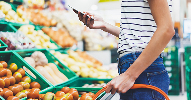 woman shopping for groceries while looking at cell phone