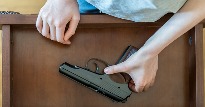 youth reaching into drawer for gun