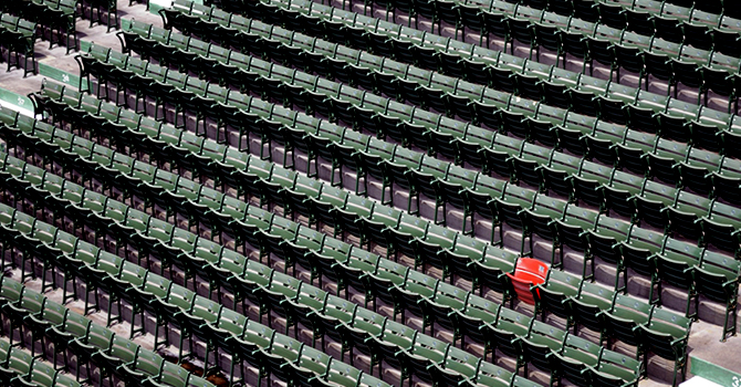An empty sports arena and lone red seat