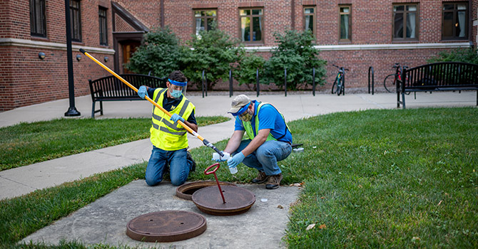 Two workers with the University of Michigan's Environment Health & Safety collect sewage samples from Stockwell Hall in the Hill Neighborhood at U-M's Ann Arbor Campus.