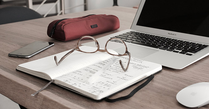 A book, glasses, phone, pencil case, and laptop on a desk.
