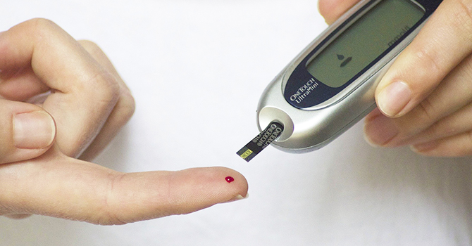 Person testing their glucose levels with a glucose meter.