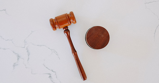 Wooden gavel on a marble table.