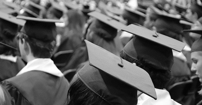 Black and white photo of students wearing a graduation cap and gown.