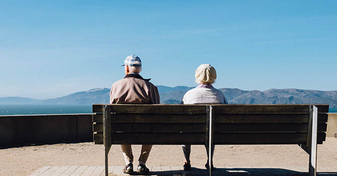 Older couple sitting on a bench outdoors.