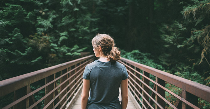 Woman on bridge in the forest.