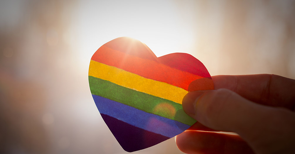 A person holding a rainbow heart sticker.
