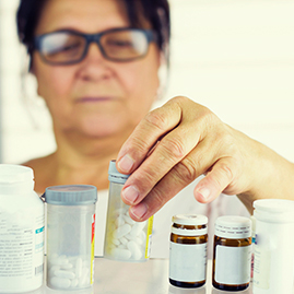 woman lookin at pill bottle in medicine cabinet