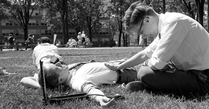 Students practice taking blood pressure on the campus lawn, May 1958. © Regents of the University of Michigan.