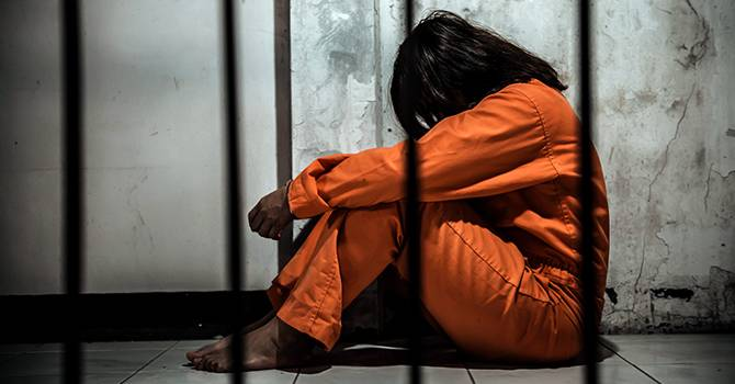 A woman in orange sits on the floor of a prison cell