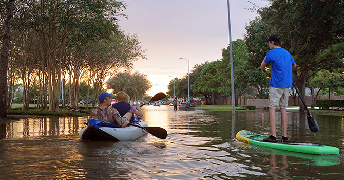 family canoeing down flooded road in Houston, Texas