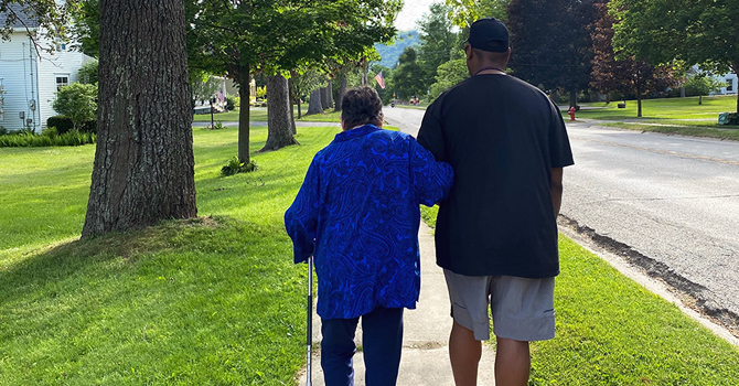 Caregiver supporting a family member on a walk
