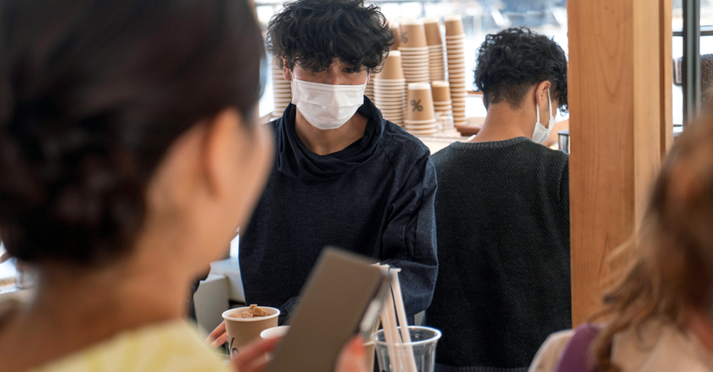 A coffee shop worker serves an unmasked customer