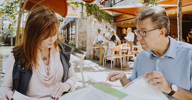 Adult daughter and father sitting at a restaurant reading paper.