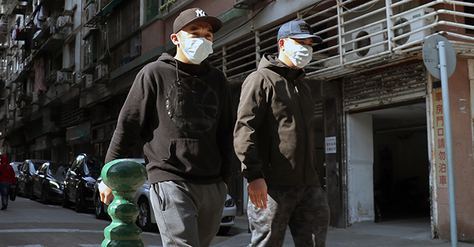 Two men walk down a street in Macau wearing face masks to protect them to be infected with coronavirus.