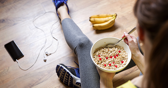 Young adult in athletic wear holding a bowl of oatmeal