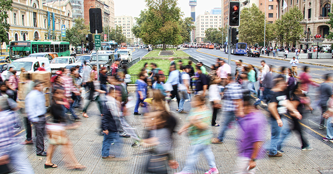 A crowd of people walking across a busy city intersection.
