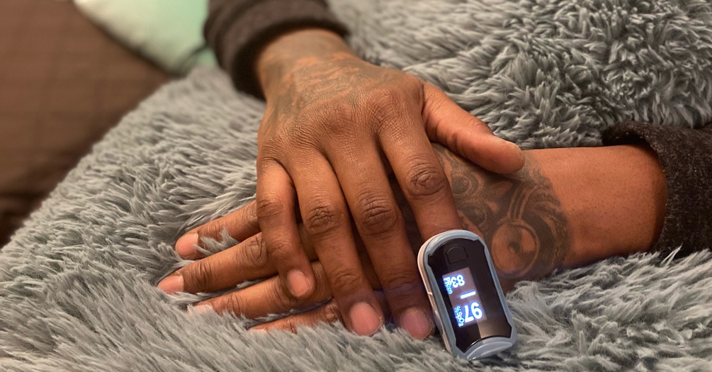 Black patient checking blood oxygen levels with a pulse oximeter