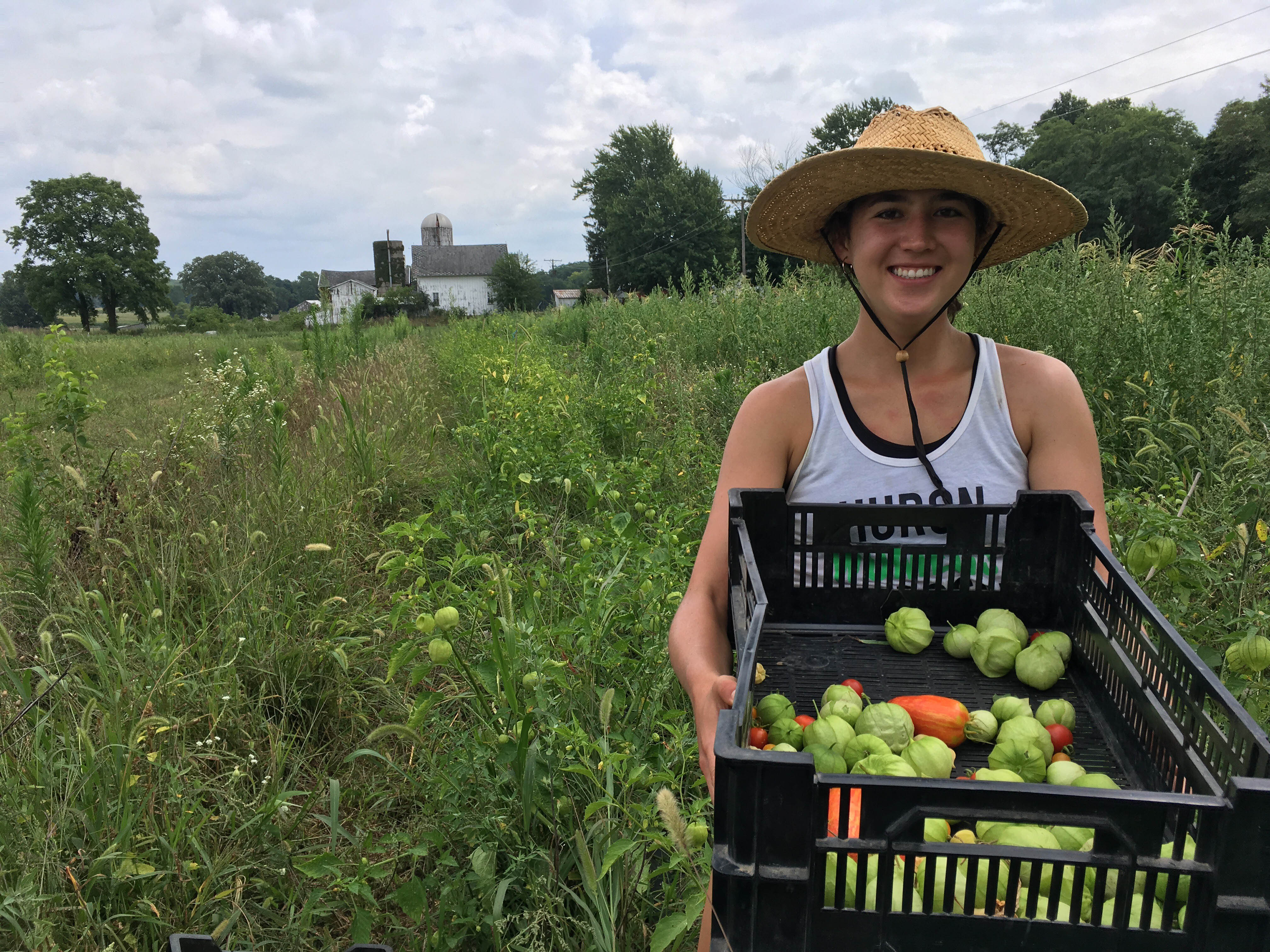 Schmitter holds seasonal produce—tomatillos and heirloom tomatoes—grown on Brines Farm, a local producer providing organic food to Southeast Michigan. Being involved in the full cycle of growing food, from planting to harvesting, is an amazing, rewarding experience, Schmitter says.